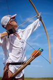 Teenager boy learns to shoot from a wooden bow. Teenager boy learns to shoot from a classic wooden bow on the beach royalty free stock image