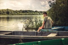 Teenager boy lonely contemplation countryside landscape on river bank during countryside summer holidays. Handsome teenager boy lonely contemplation countryside royalty free stock photography