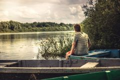 Teenager boy lonely contemplation countryside scenery on river boat during countryside summer holidays. Teenager boy lonely contemplation countryside scenery at Stock Image
