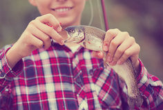 Teenager boy looking at fish on hook Royalty Free Stock Images