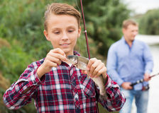 Teenager boy looking at fish on hook Royalty Free Stock Photo