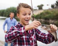 Teenager boy looking at fish on hook. Glad teenager boy holding and looking at a fish on a hook stock photo