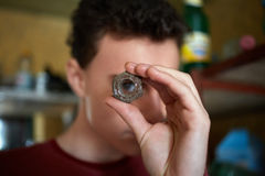Teenager boy looking through a rusty screw nut Royalty Free Stock Images