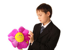 Teenager boy is looking at a toy flower Stock Image