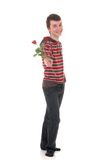 Teenager boy love. Handsome casual dressed teenager boy, giving a rose,  studio shot on reflective surface Stock Image