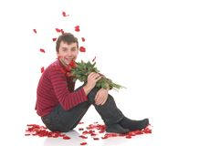 Teenager boy love. Handsome casual dressed teenager boy, surrounded with rose petals, bouquet in hand. studio shot on reflective surface Stock Photos