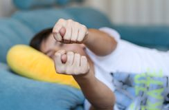 Teenager boy lying on sofa at home showing fig to parents at camera. Teen rudeness and protest. royalty free stock photos