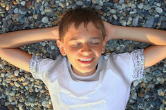 Teenager boy lying on stones, closed eyes. Teenager boy lying on stones on stone seacoast, closed eyes, holding hands behind head Stock Image