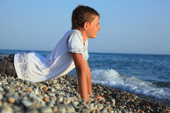 Teenager boy lying on stones on seacoast Royalty Free Stock Photography