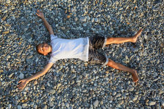 Teenager boy lying on stones on stone seacoast Royalty Free Stock Photography