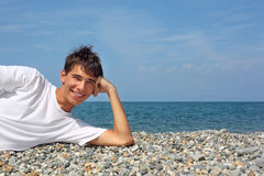 Teenager boy lying on stony seacoast Royalty Free Stock Image