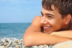 Teenager boy lying on stony seacoast, looking afar Royalty Free Stock Images