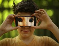 Teenager boy make funny picture with cats eyes on cell phone. Outdoor summer photo royalty free stock image