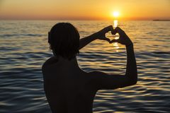 Teenager boy making the shape of heart with his hands. Silhouette of a teenager boy making the shape of a heart with his hands on a beach at sunset in summer in royalty free stock image