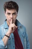 Teenager boy making silence gesture Stock Images