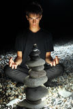 Teenager boy meditating near pyramid from pebble Royalty Free Stock Image