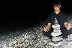 Teenager boy meditating near pyramid from pebble Royalty Free Stock Photos
