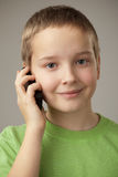 Teenager boy and mobile phone. Portrait teenager boy on a gray background Stock Photography