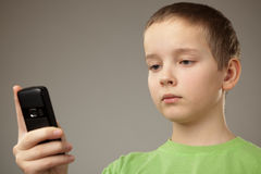 Teenager boy and mobile phone. Portrait teenager boy on a gray background Stock Photos