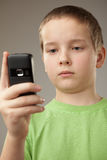 Teenager boy and mobile phone. Portrait teenager boy on a gray background Stock Photo