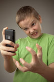 Teenager boy and mobile phone. Portrait teenager boy on a gray background Stock Images