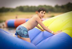 Teenager boy in open air amusement aquapark jump on trampoline. Close up photo on lake background stock photography