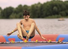 Teenager boy in open air amusement aquapark jump on trampoline. Close up photo on lake background stock image