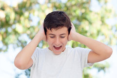 Teenager boy outdoor covering his ears Stock Images