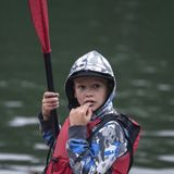 teenager boy with a paddle from a kayak sports boat stands pensively on the river bank with a finger to his mouth. stock image