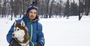 Teenager boy plaing with white Husky dog. Christmas happy teenager boy playing with white Husky dog in winter day, dog and child on snow royalty free stock photo