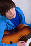 Teenager boy playing the guitar. Portrait of teenager boy playing the guitar and dreaming away Royalty Free Stock Photography