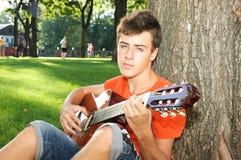 Teenager boy playing guitar at park. Romantic teenager boy playing guitar at park Royalty Free Stock Photo