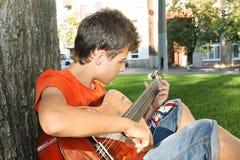 Teenager boy playing guitar at park. Teenager boy playing guitar at the park Royalty Free Stock Image