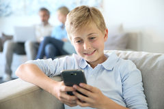 Teenager boy playing with smartphone at home Stock Photos