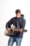 Teenager boy plays at acoustic guitar with much feeling Royalty Free Stock Image