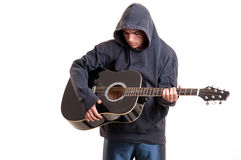 Teenager boy plays at acoustic guitar with much feeling Royalty Free Stock Photos