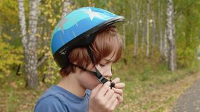 Teenager boy putting bicycle helmet on head in autumn park. Handsome boy wearing blue protective helmet for. Skateboarding in sport park stock footage