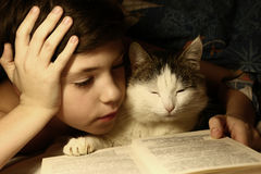 Teenager boy reading book in bed with sleeping cat Royalty Free Stock Images