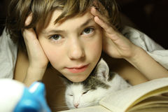 Teenager boy reading book with cat in bed. Close up photo, kid and cat Royalty Free Stock Image