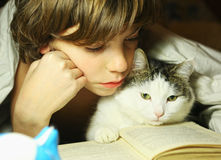 Teenager boy reading book with cat in bed. Close up photo, kid and cat Stock Photos