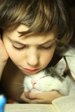 Teenager boy reading book with cat in bed. Close up photo, kid and cat Royalty Free Stock Photo