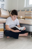 Teenager boy reading a book in room Stock Photo