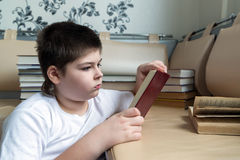 Teenager boy reading a book in room Stock Photos