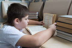 Teenager boy reading a book in room Stock Images