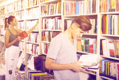 Teenager boy reading book in shop Royalty Free Stock Images