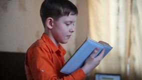 Teenager boy reading a book ten years looking stock video footage