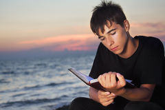 Teenager boy reads book sitting on beach Stock Image