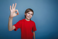 Teenager boy in red shirt showing OK sign on a Royalty Free Stock Image