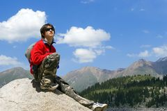 Teenager boy in red sport pullover in mountain. Teenager in red sport pullover in mountain hike and sky Stock Photo