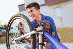 Teenager boy repair tire on bicycle Royalty Free Stock Photos